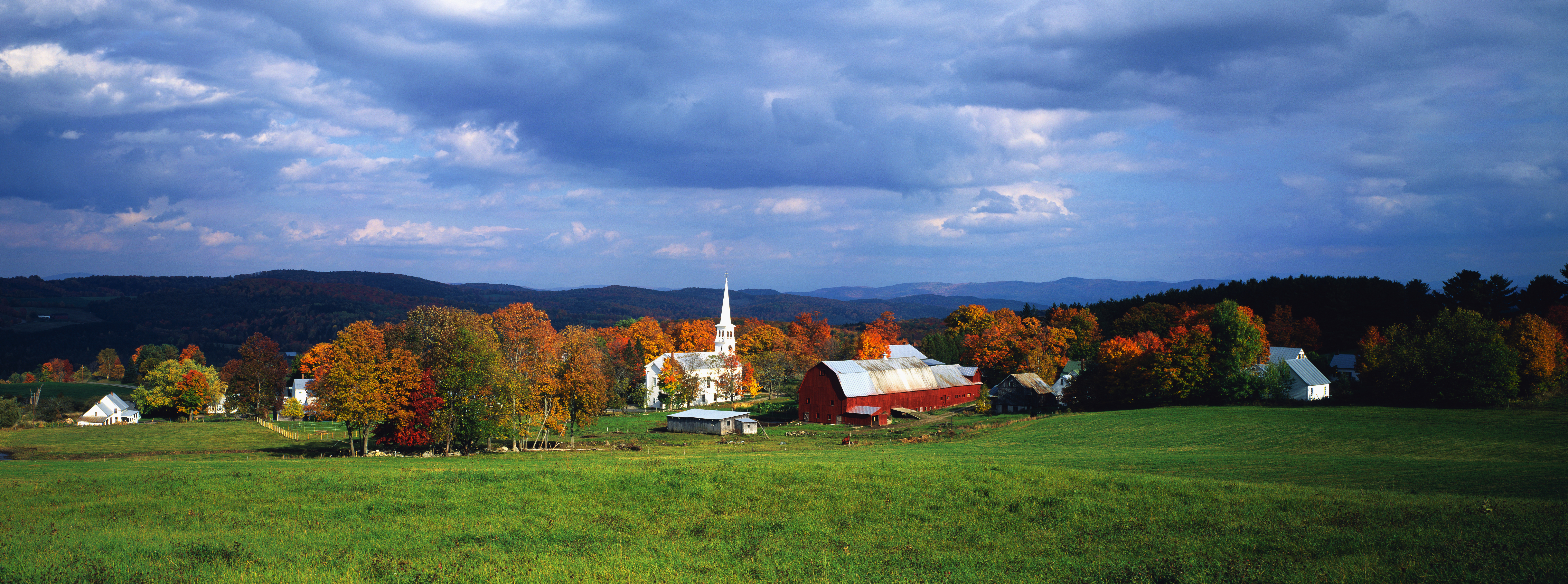 white church with steeple, red barn and pasture land in countryside scene